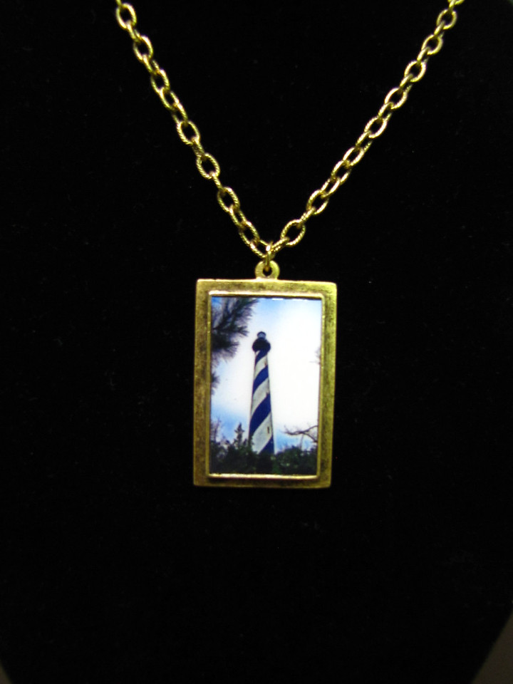 "- Cape Hatteras Lighthouse - Fine Art Photography Pendant -<br /> Buy This Item: <a href=""http://www.etsy.com/listing/74448914/cape-hatteras-lighthouse-fine-art"">http://www.etsy.com/listing/74448914/cape-hatteras-lighthouse-fine-art</a><br /> <br /> All Photography Prints and Prints of Scherenschnitte Paper Cuttings Can Be Mounted On A Pendant.<br /> <br /> The offer on this page is for a Fine Art Photography Pendant - featuring<br /> The Cape Hatteras Lighthouse -by Dave Lynch.<br /> <br /> See the original fine art print here: <a href=""http://www.etsy.com/listing/74470643/cape-hatteras-lighhouse-fine-art"">http://www.etsy.com/listing/74470643/cape-hatteras-lighhouse-fine-art</a><br /> <br /> About The Pendant:<br /> This art photo pendant is set in 100% lead-free pewter and plated with antique gold.<br /> Printed on a beautiful metallic paper and sealed with a clear glass like overlay for protection and shine. The pendant measures 20 x 30mm. This offer is for the pendant only. The necklace is shown for illustration only and is available separately.<br /> <br /> This would make a unique gift for that special someone...even yourself!<br /> <br /> ~Have a special size or request? Just e-mail me and we'll see what we can work out!<br /> <br /> Or email us YOUR PHOTO and have it mounted on an art pendant gold or silver plated pewter ArtGalleryRiverRd@gmail.com"
