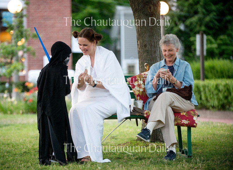 """Jennifer Maddux, dressed as Princess Leia, shows a photo on her phone to Tucker Patsey, 5, as her mother Cheryl Steiner sits nearby following a Star Wars costume contest held before an outdoor screening of """"The Force Awakens"""" on Bestor Plaza Tuesday, July 19, 2016."""