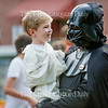 "Matt Ewalt, Associate Director of Education and Youth Services, carries his son Connor Ewalt, dressed as Luke Skywalker, at the conclusion of a Star Wars costume contest held before an outdoor screening of ""The Force Awakens"" on Bestor Plaza Tuesday, July 19, 2016."