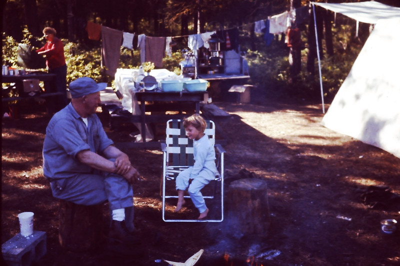 "Frank Raymond & Pauli Yaden - 1962 - Uncle Frank (age 53) and Pauli (age 4) discuss the issues of the day by fireside as Aunt Evelyn organizes in the background - Twin Lakes camping excursion - Twin Lakes, WA (From the Bernard Shaw 35mm Slide Collection)<br /> <br /> Note from Sister Pauli:<br /> <br /> I love Uncle Frank and the Twin Lakes adventures, especially the fond<br /> memory of me ""accidentally"" hitting Mark in the back of the head with a<br /> rock...oops!"