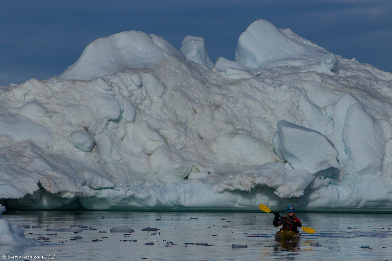 Kayaking in Greenland near an iceberg
