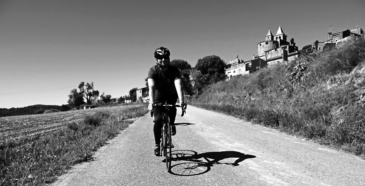 black and white photo of cyclist in front of castle