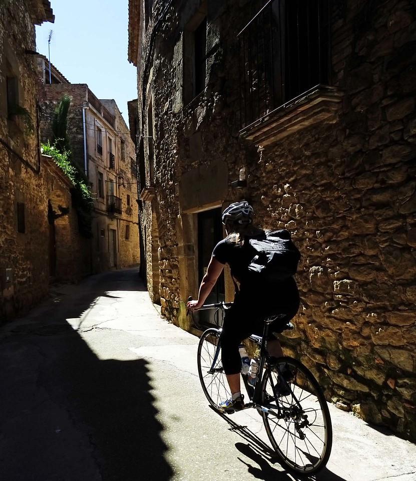 cyclist riding through european village