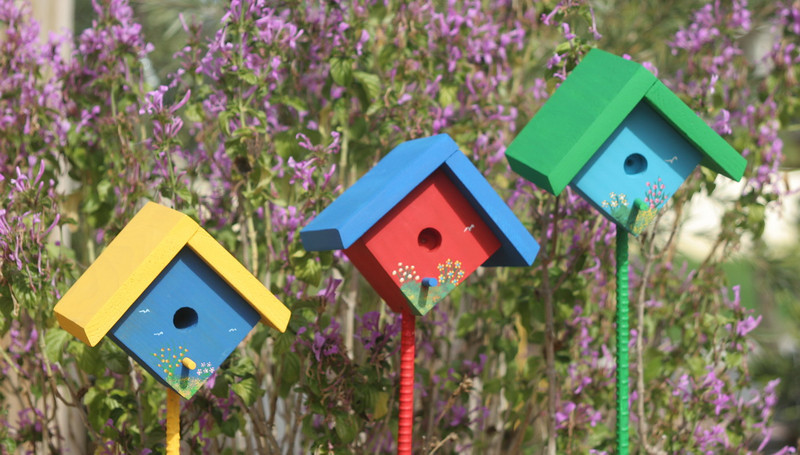 """These small ornamental birdhouses add a splash of color to your garden.  They are 4 1/2"""" square and come with a 3' pole, which you easily push into your soil.  They are hand painted with a floral design and they are perfect for people who want birdhouses in their garden, but do not necessarily want to attract birds due to the presence of a loveable dog or cat."""