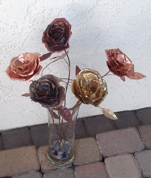 Five copper and brass roses.