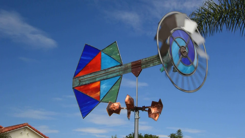 This guitar-like whirligig combines copper, stainless steel,  stained glass  and some repurposed piano strings.