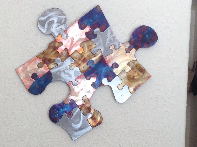 Jigsaw jigsaw is a piece inspired by jigsaw puzzles.  A jigsaw puzzle of a jigsaw piece combining copper, stainless steel, steel using heat coloring techniques.