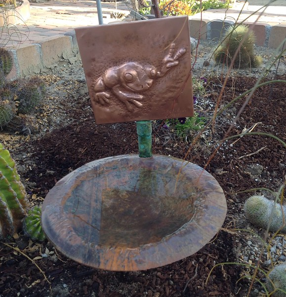 A copper birdbath combining a repousse frog and a hand hammered vessel.
