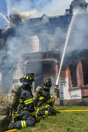 Fitchburg Firefighter Skyler Kozloski and Kevin Machado work a hand line on the A side of the building.