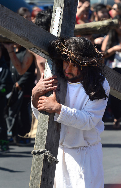 . Jesus, played by Alfonso Sandoval, carries a cross during a Good Friday commemoration of the Stations of the Cross, also known as The Way of the Cross, or Via Crucis at St. Mary of the Nativity Catholic Church in Salinas Friday March 25, 2016. (David Royal - Monterey Herald)