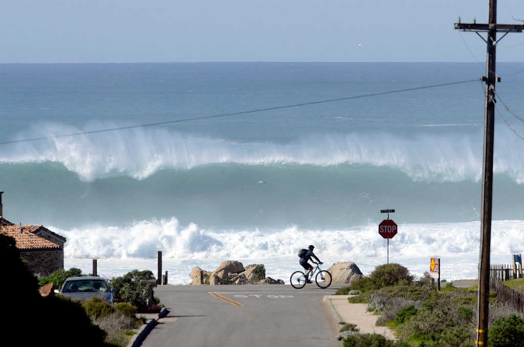 . A cyclist rides along Sunset Drive as large El Niño fueled waves hit the coastline in Pacific Grove on Thursday February 4, 2016. (David Royal - Monterey Herald)