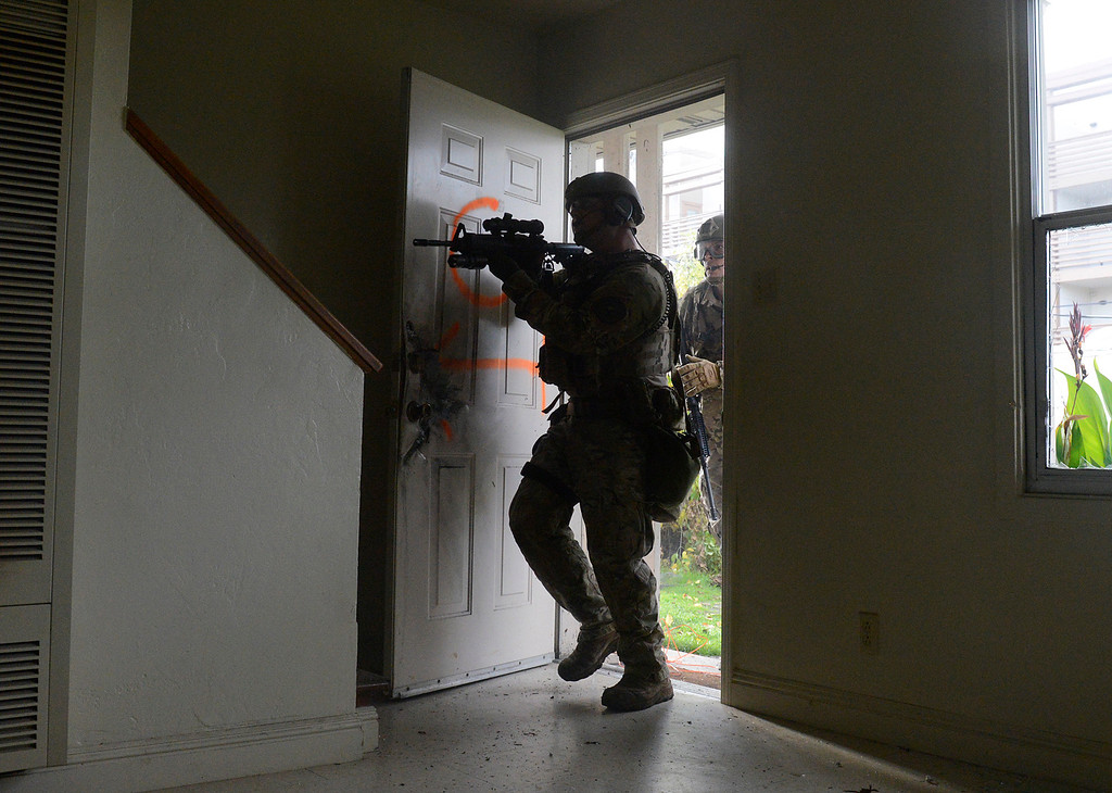 . Monterey County Sherriff\'s Department SWAT team storm an apartment after busting the door open with a explosive charge during a training session in vacant public housing on East Rossi Street in Salinas on Friday December 9, 2016. The structures are slated to be torn down and replaced with new energy efficient affordable apartments. (David Royal - Monterey Herald)