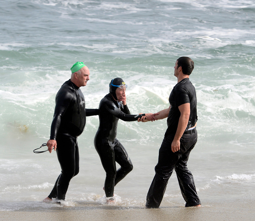 . Jim Sapia, left, and another man help a fellow member of the Kelp Krawlers swim club out of the water on after she was rescued during a swim in large surf at Lovers Point in Pacific Grove on Sunday November 6, 2016. The woman was towed in by other swimmers after currents had pushed her toward rocks.  (David Royal - Monterey Herald)