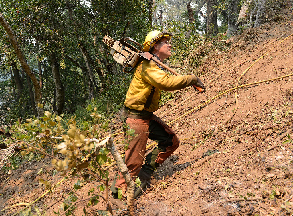 . Timber faller Jeff Turpin hikes up a steep hillside with his chainsaw while cutting a fire break for the Soberanes Fire in Rancho San Carlos in Carmel Valley on Saturday July 30, 2016. (David Royal - Monterey Herald)