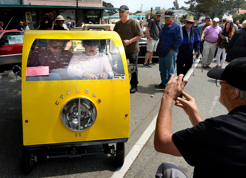 . Juliana Hoewing reacts after accidentally hitting the gas causing the 1960 Martini Cyclops her and her husband Robert were having their photo taken in to lurch forward during the Little Car Show in Pacific Grove on Wednesday August 17, 2016.  At right is the car\'s owner James Ducoing. (David Royal - Monterey Herald)