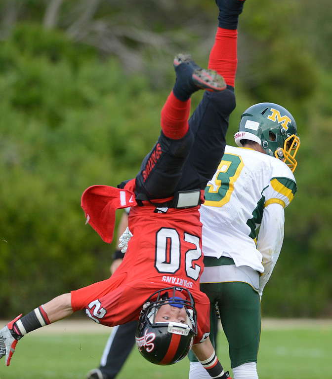 . Seaside\'s Daniel Sayre flips through the air after breaking up a pass intended for Monterey\'s Marcus Dorn (3) during the Battle of the Bay football game in Seaside on Saturday November 5, 2016. (David Royal - Monterey Herald)