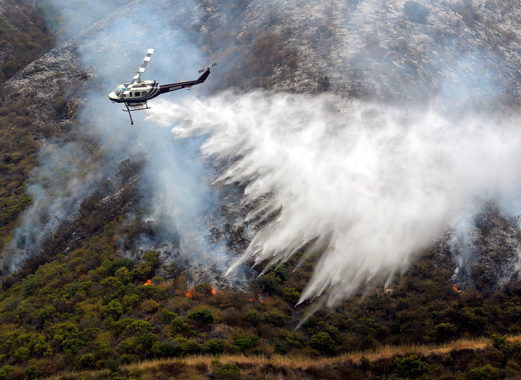 . A helicopter makes a water drop near the Mount Manuel Trail while fighting the Soberanes Fire near the the Big Sur village on Thursday August 11, 2016. (David Royal - Monterey Herald)
