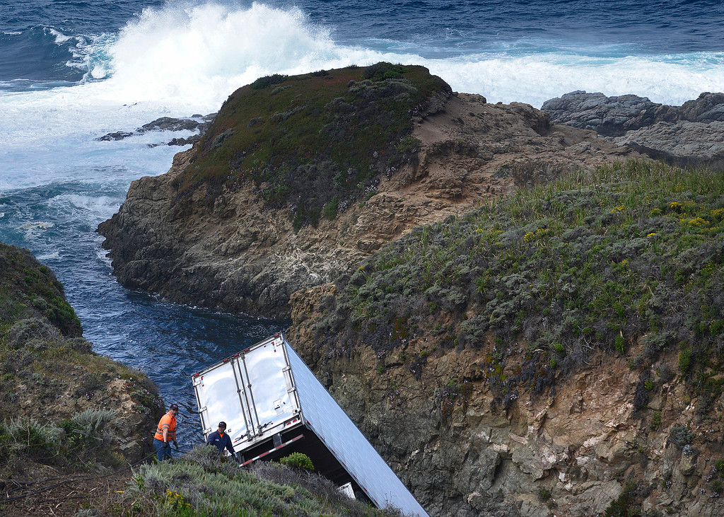 . Tow crews work to connect cables to a big rig hanging from cliffs down toward the waters edge on the Big Sur Coast on Friday May 20, 2016. Loaded with strawberries, the truck went off  southbound Highway 1 Thursday night south of Soberanes Point. (David Royal - Monterey Herald)