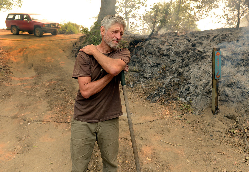 . Theo Maehr pasuses while extinguishing his burning house number and other hotspots near his home in Palo Colorado Canyon on the northern Big Sur Coast on Monday July 25, 2016. (David Royal - Monterey Herald)