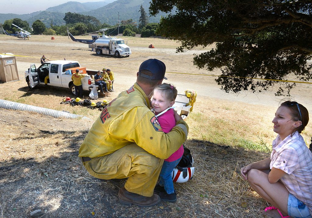 . Cal Fire Helitack captan Richard Brechbuehl gets a hug from Kaitlyn Tousey, 3, as her mother Emily looks on, after he returned from a mission to battle the Soberanes Fire at the old Carmel Valley airport on Tuesday August 2, 2016. (David Royal - Monterey Herald)