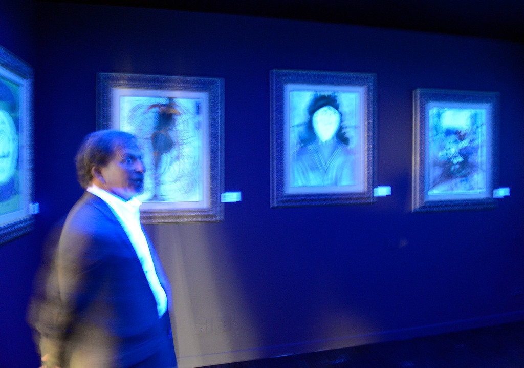 . Dali 17 Gallery volunteer Michael Carbaugh looks over works of Salvador Dali in the Black Light Room during the private opening and VIP reception for the  in the former Maritime Museum in Monterey on Thursday July 7, 2016. The Dali collection was made possible through a partnership with Pebble Beach Businessman Dmitry Piterman and the Monterey History and Art Association.  (David Royal - Monterey Herald)