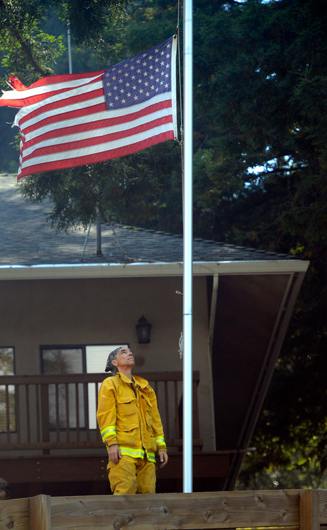 . Midcoast Fire Brigade voulnteer firefighter Scott Bogen looks up after lowering the American flag to half mast in honor of bulldozer operator Robert Reagan at the Palo Colorado Canyon fire station at in Big Sur on Thursday July 28, 2016. Reagan died Tuesday night when his bulldozer rolled while fighting the Soberanes Fire. (David Royal - Monterey Herald)