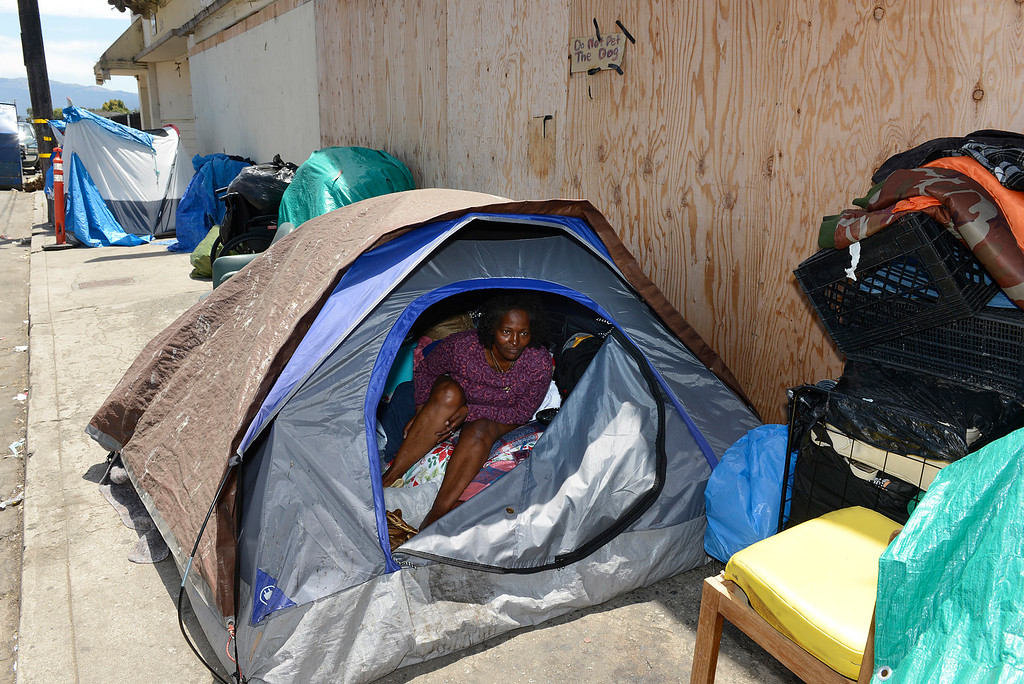 . Verna Mae Hacker puts moisturizer on her legs while sitting in her tent on Soledad Street after showering inside Dorothy\'s Place shelter in Chinatown in Salinas on June 2, 2016. More than two months have passed since Salinas administrators razed dozens of encampments in Chinatown where people used to make their homes.(David Royal - Monterey Herald)