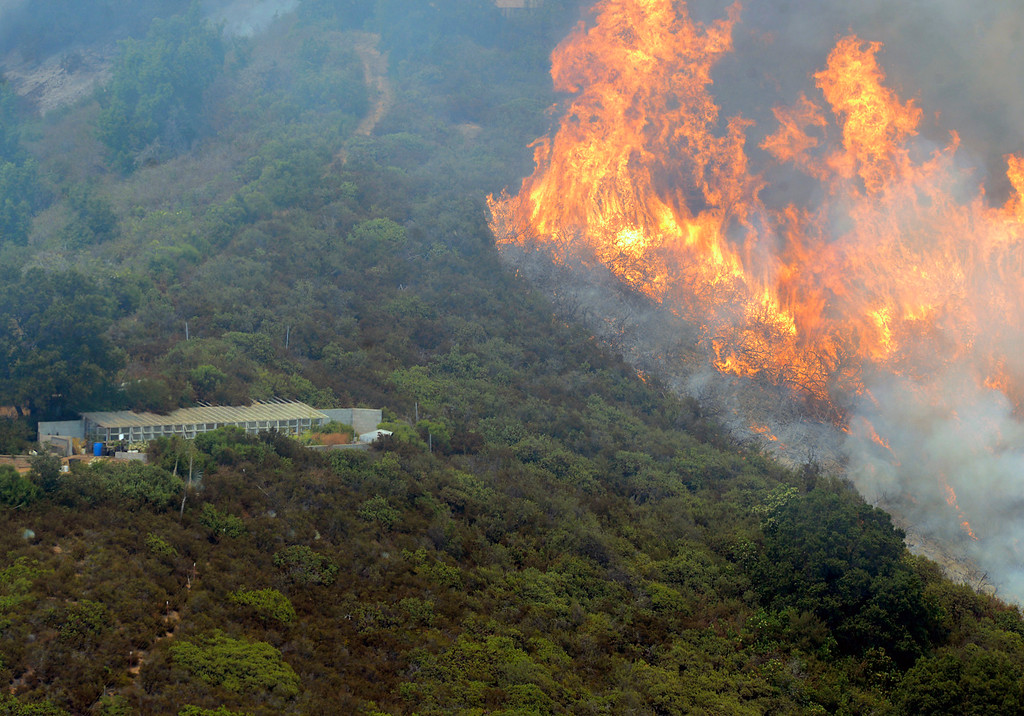 . Flames from the Soberanes Fire engulf a hillside near a structure in Palo Colorado Canyon on the northern Big Sur Coast on Monday July 25, 2016. (David Royal - Monterey Herald)