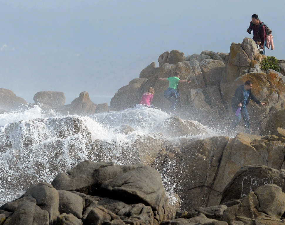 . A wave swamps young families on the tip of Lovers Point as large surf batters Pacific Grove on Sunday November 6, 2016. The current swell is predicted to back down into Monday before a new swell builds on Tuesday acccording to the National Weather Service.  (David Royal - Monterey Herald)