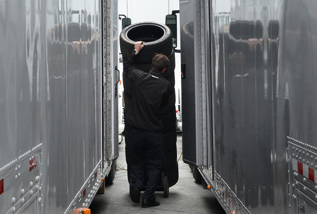 . Ryan Haley, tire pit crew member for Bimmer World Next Level European race team, wheels tires between trailers during the Monterey Grand Prix at Laguna Seca Raceway in Monterey on Friday April 29, 2016. (David Royal - Monterey Herald)
