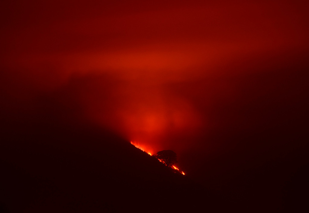 . Flames from the Soberanes Fire illuminate the night above Rancho San Carlos in Carmel Valley on Tuesday July 26, 2016. (David Royal - Monterey Herald)