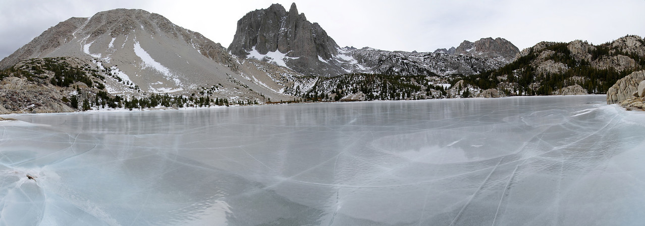 Panoramic view of the frozen-over Second Big Pine Lake with the Temple Crag in the background.