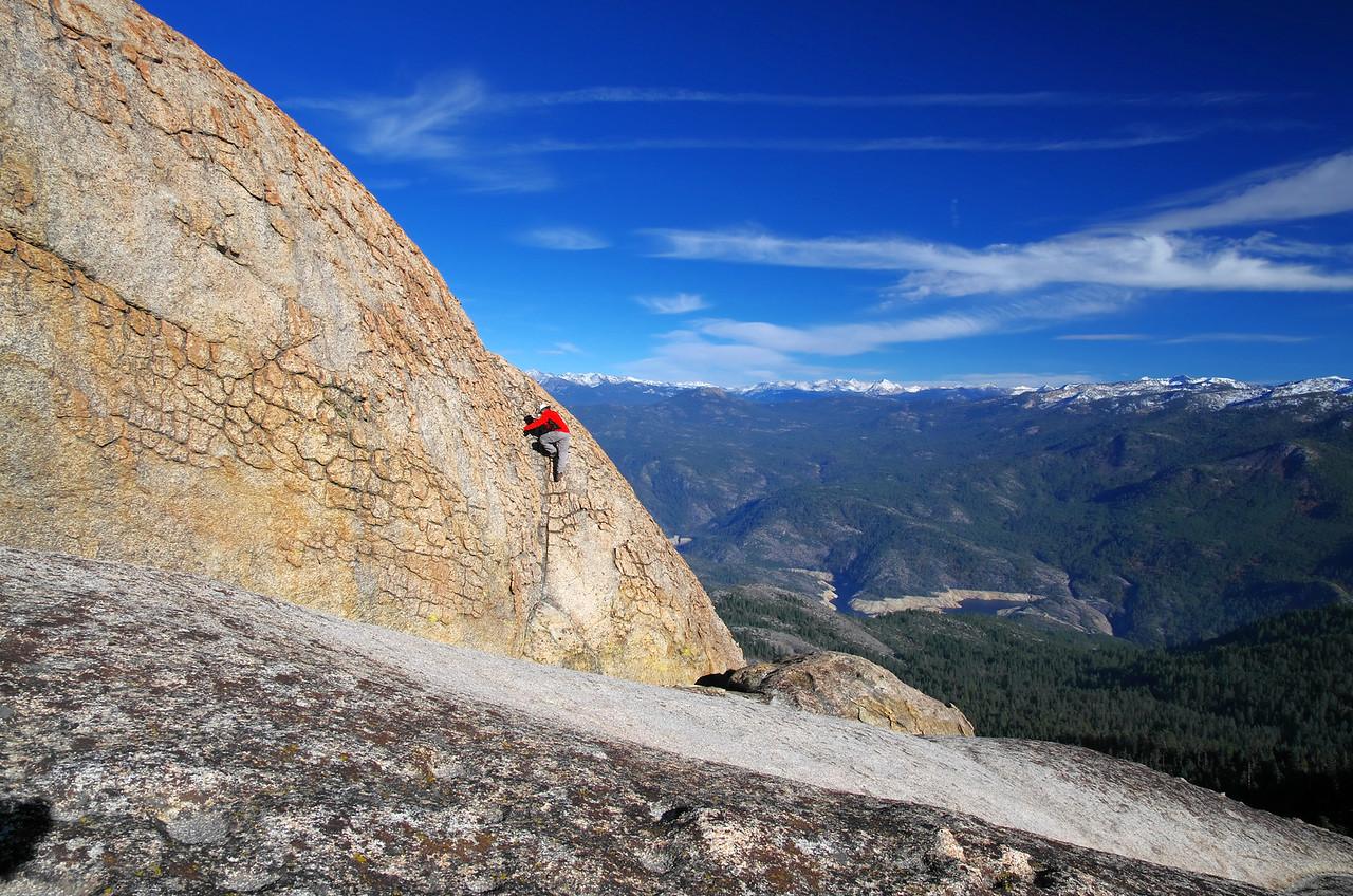 Climbing the summit block of the lower Eagle Beak Peak; Mammoth Pool Reservoir in the background.