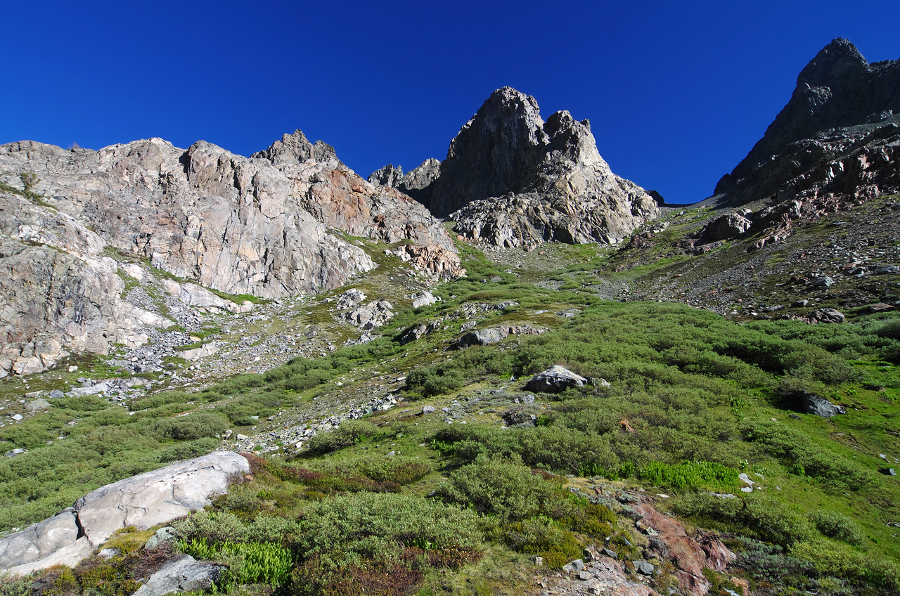 As I continue to ascend the grassy southern slope extending from Minaret Lake to the summit of Volcanic Ridge, I notice another possible approach to the left that may lead me to a better view of the Mammoth Minarets than the near-true summit that I climbed in June of 2002.