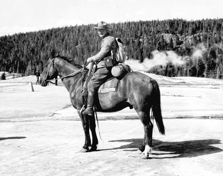 George Grant on horseback with camera and tripod, Yellowstone, 1933