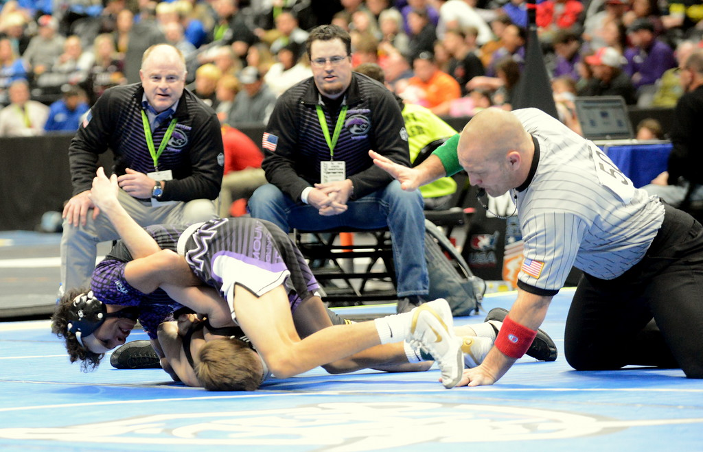 . The referee moves in to stop the match as Malachi Contreras starts to roll Thompson Valley\'s Airiel Siegel with a double arm bar in their 4A 120-pound semifinal match at the Colorado state wrestling tournament Friday night at the Pepsi Center in Denver. Contreras scored an 8-0 major decision. (Mike Brohard/Loveland Reporter-Herald)