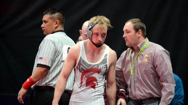 Berthoud's Austyn Binkly listens to assistant coach Robby Workman after getting his bloody nose stopped in his 3A 145-pound semifinal match with Olathe's Clay Yarnell at the Colorado state wrestling tournament Friday night at the Pepsi Center in Denver. (Mike Brohard/Loveland Reporter-Herald)