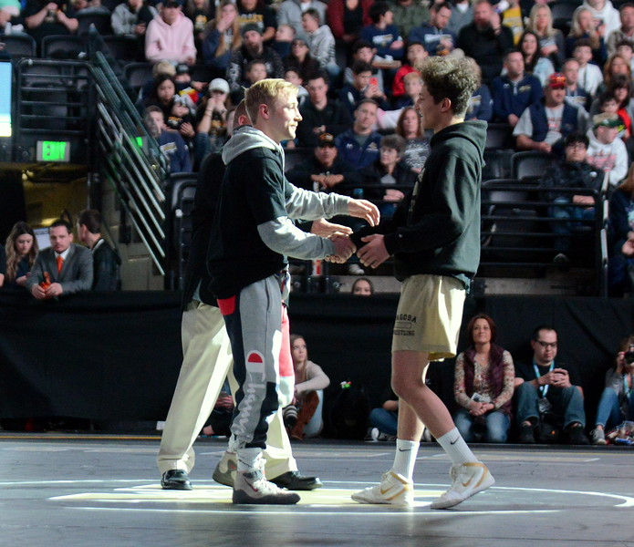 Austyn Binkly of Berthoud shakes hands with Cameron Lucero of Pagosa Springs during introductions at Saturday's finals of the Colorado State Wrestling Tournament at the Pepsi Center in Denver. (Mike Brohard/Loveland Reporter-Herald)