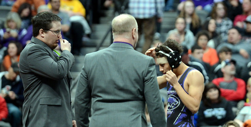 Mountain View's Malachi Contreras puts on his headgear as coaches Shawn Hart (left) and Scott Pickert look on prior to his 4A final at 120 pounds at Saturday's finals of the Colorado State Wrestling Tournament at the Pepsi Center in Denver. (Mike Brohard/Loveland Reporter-Herald)