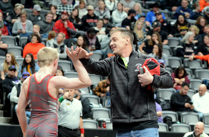 Loveland coach Troy Lussenhop gives Kobi Johnson a high-five after the freshman placed third at 106 pounds in 4A on Saturday at the state wrestling tournament at the Pepsi Center in Denver. (Mike Brohard/Loveland Reporter-Herald)