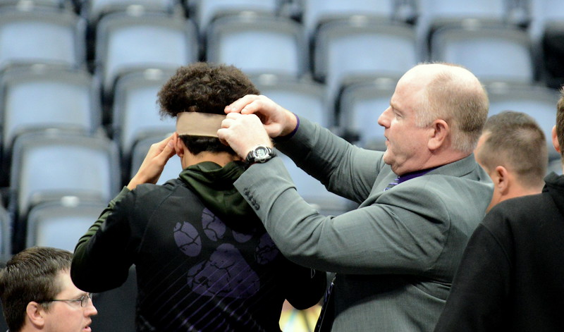 Mountain View coach Scott Barker tapes Malachi Contreras' head during warmup for Saturday's finals of the Colorado State Wrestling Tournament at the Pepsi Center in Denver. Contreras sustained a gash over his left eye in regionals which require eight stitches. (Mike Brohard/Loveland Reporter-Herald)