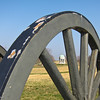The Maryland State Monument, the only one dedicated to both Union and Confederate soldiers, is visible through the spokes of a cannon wheel.