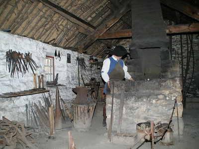 The blacksmith is hard at work at the Ulster forge located near the Scotch-Irish farm.