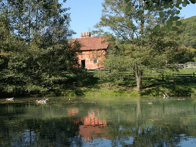 A glimpse of the English farmhouse from the pond near the Ulster forge.
