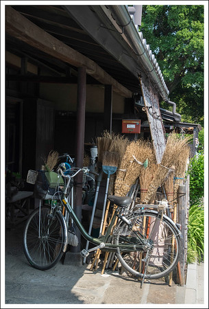 Brooms, bicycles and a mailbox.