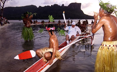 The Sydney 2000 Olympic Torch Relay continues it's journey through Oceania. 24 May 2000 - 6.25pm,  Federated States of Micronesia Traditionally dressed men blow shell horns to signal the arrival of the second last torchbearer for the day, Vice President Redley Killion, after canoeing past Sokehs Rock (in the background) to land on Misko Beach . The Olympic torch is spending a day in FSM  on it's way to Sydney  for the opening ceremony of the Sydney 2000 Olympic Games credit - photo Greg Garay/SOCOG