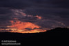 A hole in the grey clouds reveals brilliant pink clouds above, seen over a silhouetted mountain ridge with trees (11/2/2013, Wrights Rd.)<br /> EF100-400mm f/4.5-5.6L IS USM @ 135mm f5.7 1/197s ISO1600