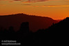 Red sunset light streams through a backlit valley, producing a silhouetted mountain ridge in front of a hazy mountain (11/2/2013, Wrights Rd.)<br /> EF70-200mm f/2.8L IS II USM @ 200mm f8 1/332s ISO250