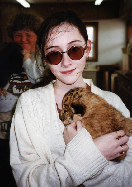 Me, with frazzly hair and ridiculously huge glasses . . . and a lion cub! I don't know the year.