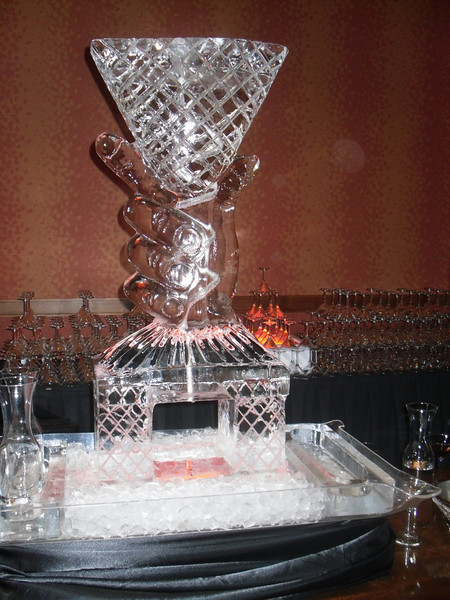 Hand holding Martini Glass custom Ice Luge with coil hose frozen in ice
